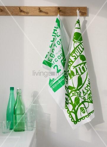 Bedruckte Geschirrtücher in Grün-Weiss an Wandhakenleiste über Küchenzeile mit Flaschen