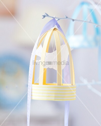 Paper bird cage on white twig
