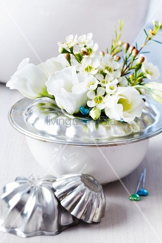 Base of bundt tin on bowl used as vase for waxflowers & lisianthus