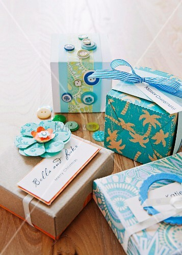 Gift boxes decorated with colourful buttons, paper flower and card tag reading Merry Christmas