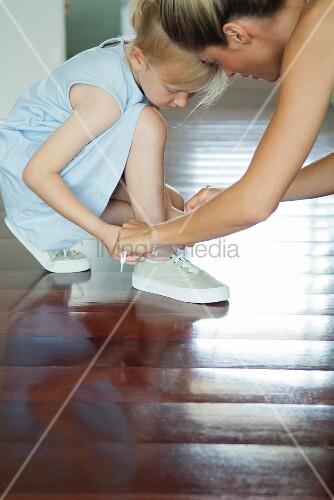 Mutter bindet kleiner Tochter die Schuhe zu