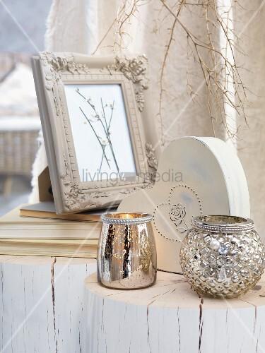 Silberne Windlichter und Bilderrahmen auf geweisselten Baumstümpfen