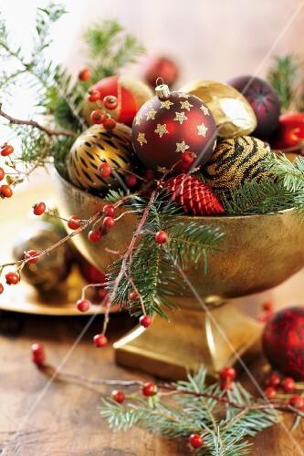 weihnachtskugeln auf tannen und beerenzweigen in vergoldeter schale bild kaufen living4media. Black Bedroom Furniture Sets. Home Design Ideas