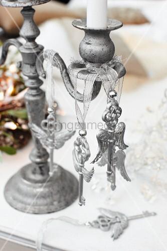Metall Kerzenständer mit aufgehängten Schlüsselobjekten auf Tisch