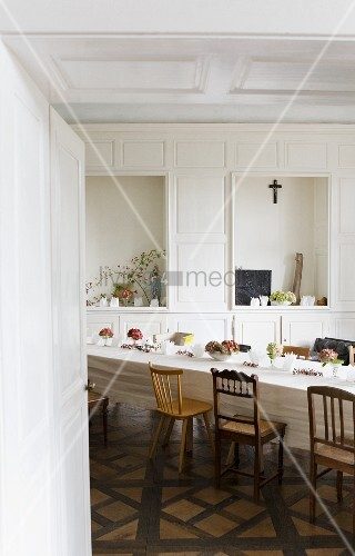 Table set in white in the dining hall of a former monastery