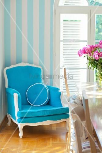 Blauer antiker Armstuhl neben einem Rundbogenfenster
