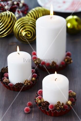 Stumpenkerzen mit Weihnachtsdeko in Törtchen-Formen