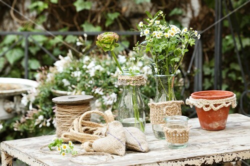 Hand-sewn hessian sachets and glass vessels with knitted covers on rustic garden table