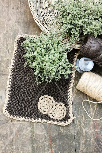 Hand-made pot holder next to reels of yarn & posies of herbs in wicker dish