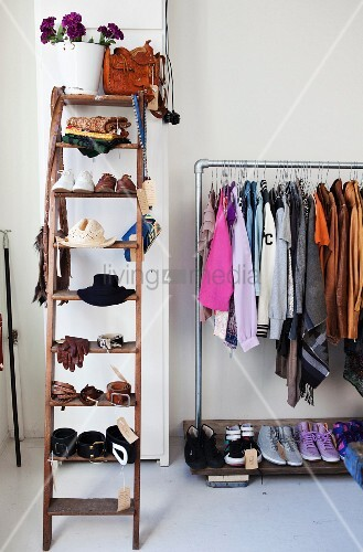 Old wooden ladder used as storage for ladies accessories; next to it a metal clothes rack with clothes hanging from it