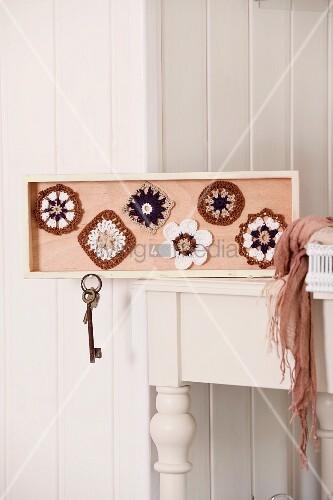 Selbstgemachtes Schlüsselbrett mit Häkelspitzen dekoriert