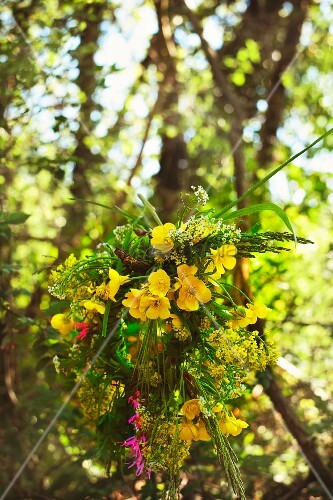 Wreath of summer flowers, mainly yellow, against blurred tapestry of trees