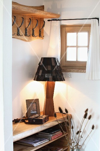 Artistic table lamp with wooden base and leather lampshade below country-house coat rack