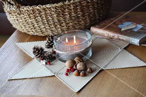 Star made of leather triangles stitched together as festive mat for candle arrangement; woven basket in background