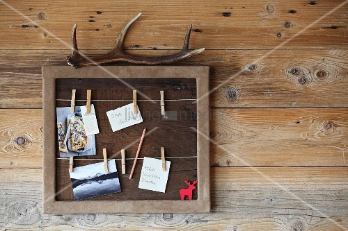 Small, hand-crafted pin board with cards and clothes pegs on cords and antler resting on top