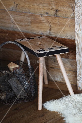 Stool with black decorative crosses and wire basket of firewood