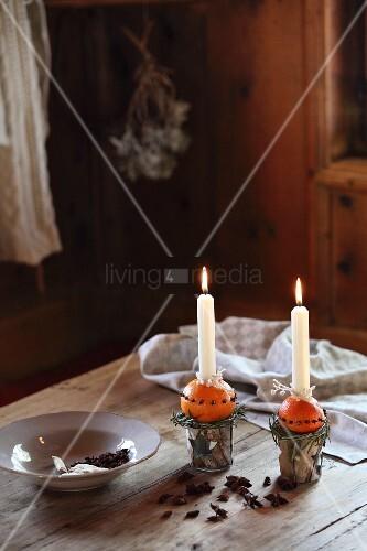 Selbstgemachte Kerzenständer mit brennenden Kerzen auf gespickten Orangen und Teller auf Holztisch in adventlicher Hüttenstimmung