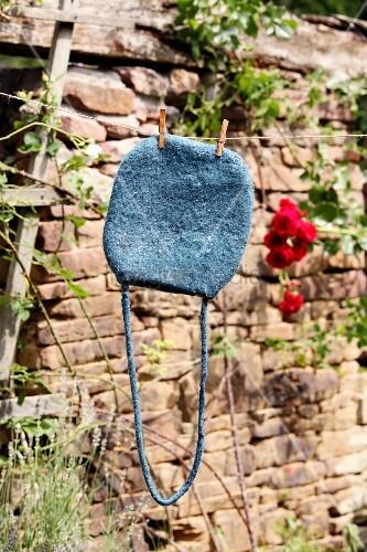 Selbstgemachte Filztasche hängt zum Trocknen auf der Leine