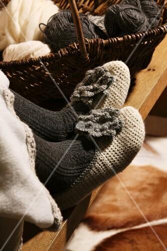Selbstgehäkelte Hausschuhe an den Füssen einer Frau neben Wollknäuel im Korb