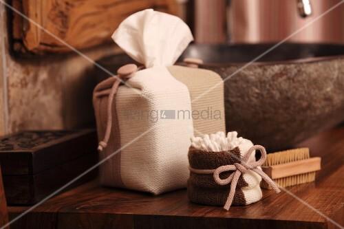 Badutensilien in Strickhüllen mit Schleifenbänder neben grauer Waschschüssel auf Holz Waschtisch