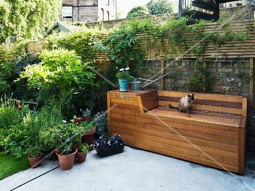 Terrasse mit Betonestrich und alter Backsteinmauer; davor eine Holzbankkonstruktion mit Stauraum für Gartengeräte und -utensilien