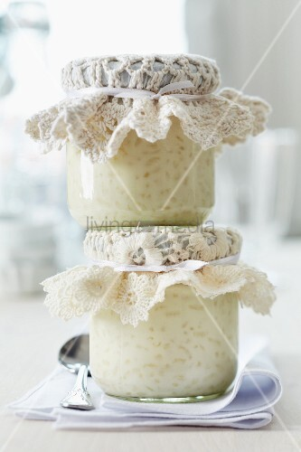 Häkeldeckchen auf Gläsern mit Milchreis als Gastgeschenk