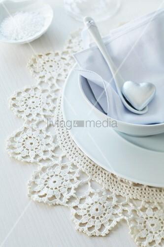 Romantisches Gedeck mit Silberherz auf Porzellanlöffel und Häkeldeckchen als Tischset