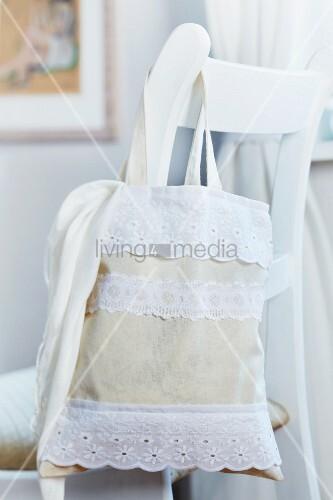 Mit aufgenähten Spitzenbändern romantisch verzierter Stoffbeutel