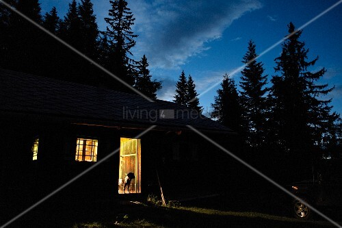 Alpine cabin at dusk with light pouring through open door