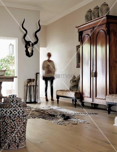 Elegantes Wohnzimmer Mit Antikem Schrank U0026 Buntem Rattankorb Vor Zebrafell  Auf Dielenboden, Im Hintergrund Frau Neben Tiertrophäe An Wand