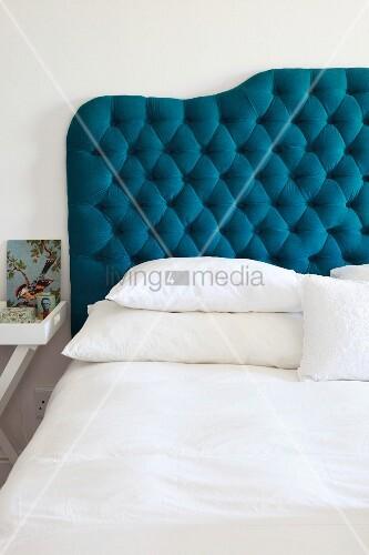 Doppelbett mit petrolfarben gepolstertem Kopfteil
