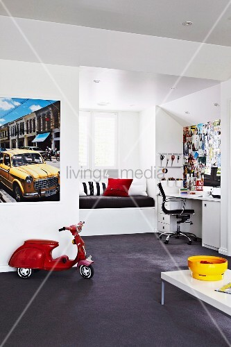 Teenager's bedroom with window seat in niche, study area with wall covered in cuttings and classic swivel chair; red toy Vespa below poster of yellow vintage car