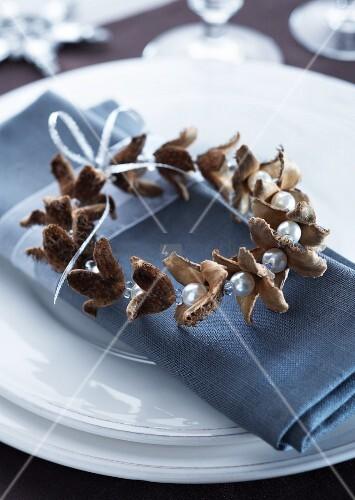 Selbstgebastelte Serviettenringe aus Bucheckernschalen und Perlen, aufgefädelt an Silberdraht