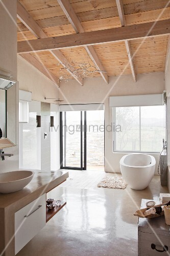 Weisses, modernes Bad mit Holzdecke und freistehender Wanne vor Fenster, daneben offene Regendusche mit Glasschiebetür ins Freie
