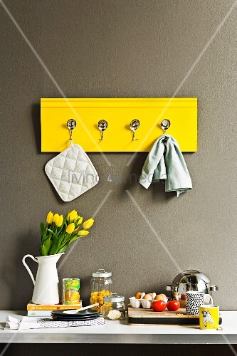 Hand-crafted yellow rack with hooks made from bent spoons on kitchen wall