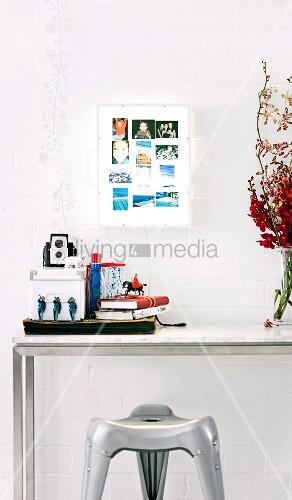 Leuchtkasten als Bilderrahmen an der Wand, darunter Metalltisch und Kunststoffhocker