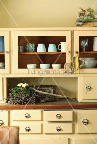 Kleines Nest aus Birkenzwiegen mit Primeln auf cremefarbenem Küchenbuffet im 50er Jahre Stil