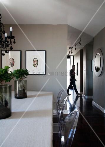 Esstisch mit künstlerischer Pflanzendeko und Ghost Stühlen; gerahmte Kunstwerke auf taupe getönter Wand und seitliche Gangflucht im Hintergrund