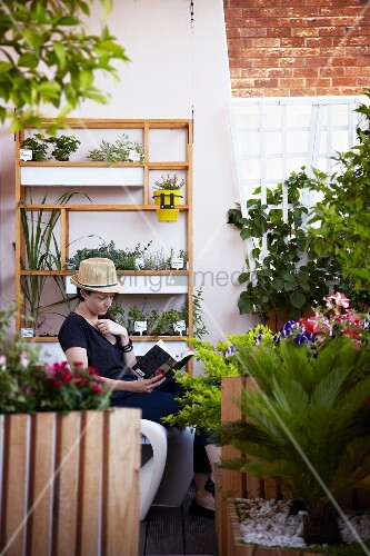 Woman reading on loft balcony with herbs on shelves, trellis and flowering plants in wooden planters