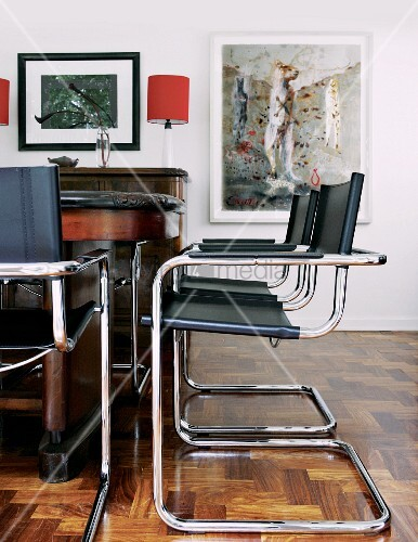 Bauhaus cantilever chairs with black leather seats and backs at antique table in traditional living room