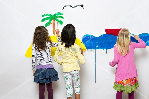 Three children painting the sea & an island on a wall