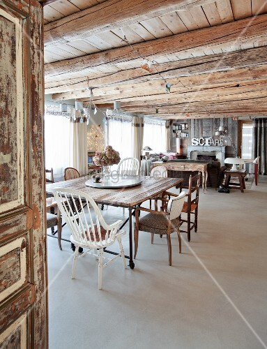 View through open door into spacious interior with various chairs and dining table below rustic wooden ceiling
