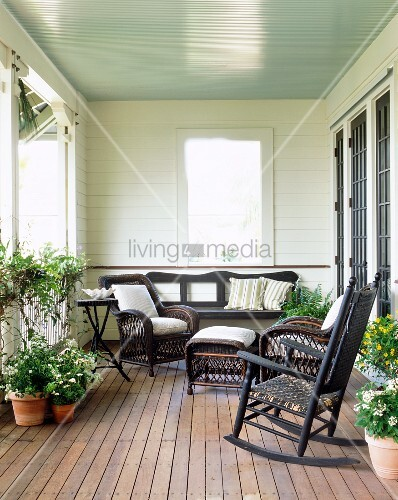 Summer porch with flowers and wicker furniture