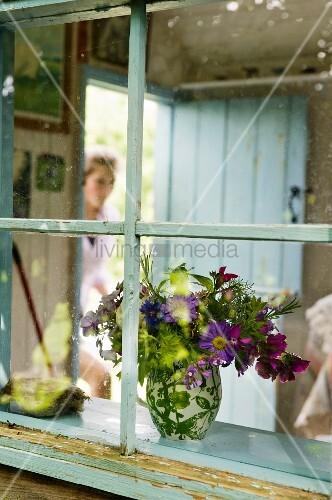 Vase of wild flowers seen through lattice window of nostalgic shepherd's hut
