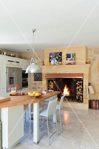 offener kamin mit integriertem brennholzlager in wohnk che mit h ngeleuchte im industriestil. Black Bedroom Furniture Sets. Home Design Ideas