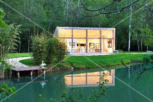 Dämmerstimmung über einem in zeitgenössischer Architektur errichteten Ateliergebäudes am Teich einer historischen Mühle in der Dordogne