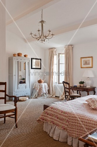 Geräumiges Schlafzimmer mit antikem Schreibtisch und Armlehnstuhl im romantischen Landhauslook