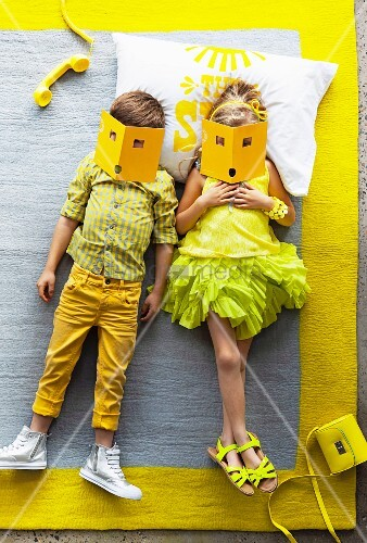 Children dressed in shades of yellow lying on grey rug with yellow border