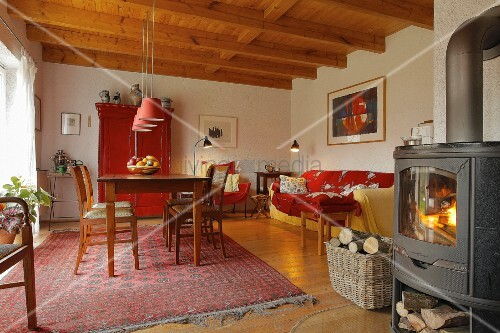 Living room in shades of red with sofa, dining table & log burner in village house (Eggelingen, Ostfriesland, Germany)