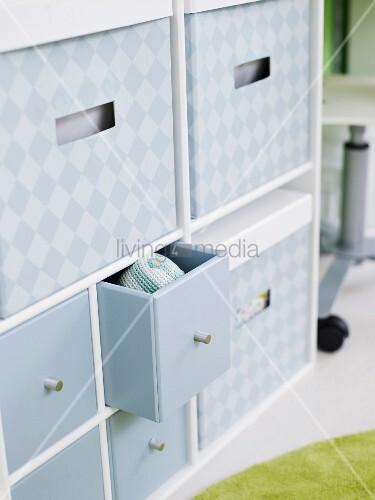Ample storage space in grey patterned boxes and small drawers in cabinet